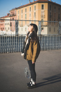 young beautiful asian hipster woman in the city - closed eyes against sun - concept serenity, freedom and emancipation