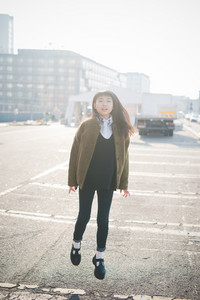 young beautiful asian hipster woman in the city - living town during sunset in backlit jumping and dancing