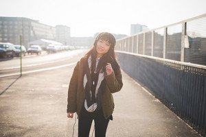 young beautiful asian hipster woman in the city - living town during sunset in backlit - listening music with headphones