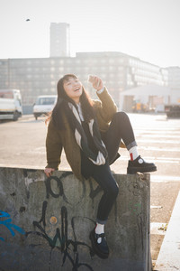 young beautiful asian hipster woman in the city - living town during sunset in backlit - sitting on a wall with smartphone