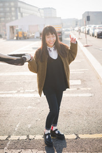 young beautiful asian hipster woman in the city - living town during sunset in backlit - smiling happy having fun with scarf