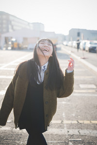 young beautiful asian hipster woman in the city - living town during sunset in backlit smiling happy having fun