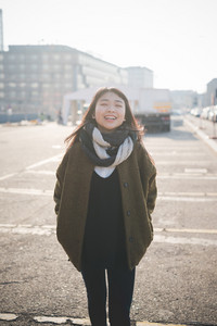 young beautiful asian hipster woman in the city - living town during sunset in backlit - smiling happy