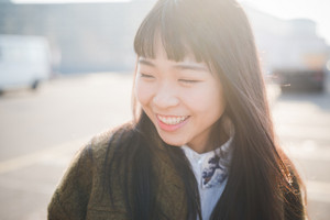 young beautiful asian hipster woman in the city - living town during sunset in backlit smiling happy