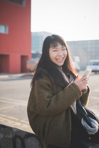 young beautiful asian hipster woman in the city - living town during sunset in backlit - using device smartphone connected online
