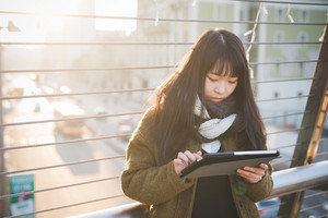 young beautiful asian hipster woman in the city - living town during sunset in backlit - using device wirelles tablet online