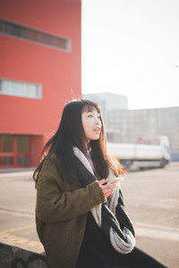 young beautiful asian hipster woman in the city - living town during sunset in backlit - using smartphone connected online