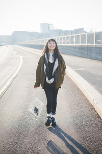 young beautiful asian hipster woman in the city - living town during sunset in backlit walking on the road