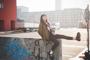 young beautiful asian hipster woman in the city - living town during sunset in backlit