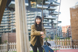 young beautiful asian hipster woman in the city - playing on a swing
