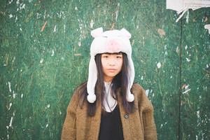 young beautiful asian hipster woman in the city - wearing funny piggy winter cap