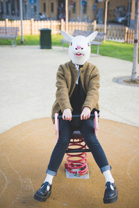 young beautiful asian hipster woman in the city - wearing rabbit mask - concept carnival, halloween, crazy