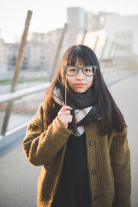 young beautiful asian hipster woman in the city - with fake eyeglasses