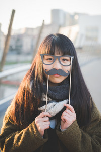 young beautiful asian hipster woman in the city - with funny fake eyeglasses and moustache