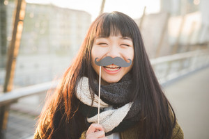 young beautiful asian hipster woman in the city - with funny fake moustache