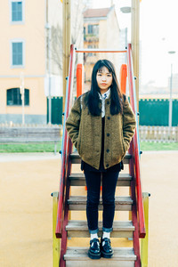 Young beautiful asian hipster woman leaning on a slide in play ground, looking in camera, pensive - serious, thoughtful concept