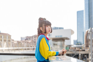 young beautiful asian millennial woman listening music with earphones and smart phone hand hold outdoor in city back light - relaxing, music, technology concept