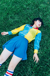 young beautiful asian millennial woman nonconformist laying on the grass relaxing - daydreaming, peaceful; death concept