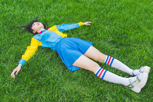 young beautiful asian millennial woman nonconformist laying on the grass relaxing - sleeping, death, relaxing concept