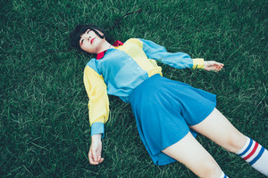 young beautiful asian millennial woman nonconformist laying on the grass relaxing -