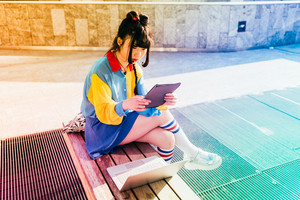 young beautiful asian millennial woman nonconformist outdoor in the city holding a tablet looking the screen - technology, social network, communication concept