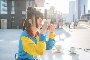 young beautiful asian millennial woman nonconformist sitting outdoor in a bar in city back light having a glass of drink, overlooking pensive - break, relaxing, happy hour concept