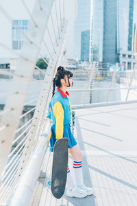 young beautiful asian millennial woman nonconformist skater posing outdoor in the city holding skateboard - eccentric, sportive concept