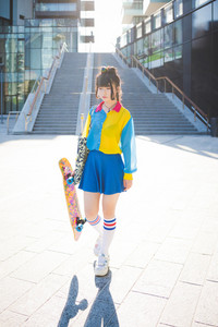 young beautiful asian millennial woman nonconformist skater walking outdoor in the city holding skateboard - eccentric, sportive concept