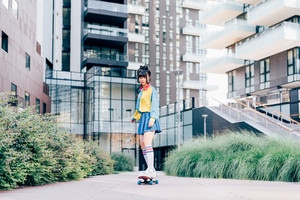 young beautiful asian millennial woman nonconformist skating outdoor in the city - skater, transport, eccentric concept