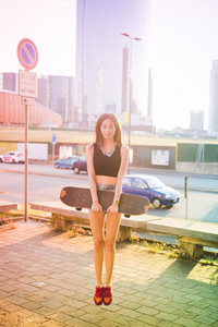 Young beautiful asian skater woman holding skateboard in city back light jumping on the spot, looking at camera smiling - sportive, jumping, happiness concept - colorful filtered