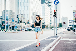 Young beautiful asian woman skater with backpack walking outdoor in the city using smart phone hand hold - technology, social network, communication concept
