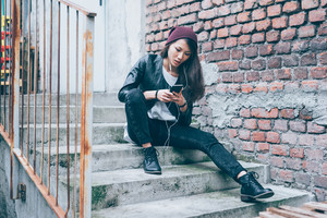 Young beautiful asiatic woman sitting on a staircase listening music with earphones and smart phone hand hold - music, technology, social network concept