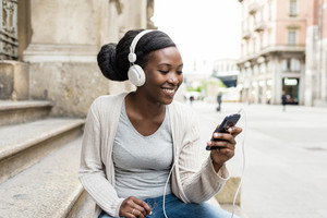 Young beautiful black woman outdoor listening music with head phones and smart phone hand hold, smiling - relaxing, happiness, technology concept