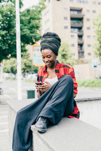 Young beautiful black woman outdoor using smart phone hand hold, smiling - relaxing, happiness, technology concept