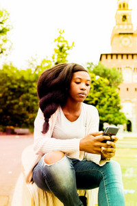 Young beautiful black woman outdoor using smart phone hand hold -  social network, happiness, technology concept