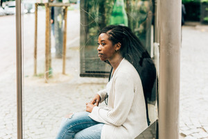 Young beautiful black woman sitting at the bus stop, overlooking - commuter, transport, going to work concept