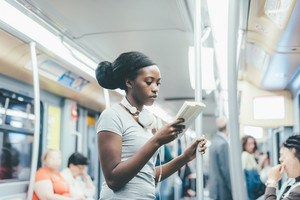 Young beautiful black woman sitting on subway reading a book - commuter, student, knowledge concept