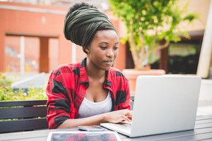 Young beautiful black woman sitting using a computer, tapping on the keyboard - university, technology, business concept