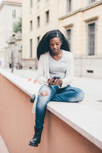 Young beautiful black woman walking outdoor in the city using smart phone hand hold, looking over serene - technology, carefree, music concept