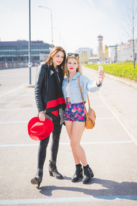 Young beautiful blonde and brunette girls having fun in the city taking selfie with smartphone - technology, vanity, social network concept