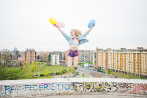 Young beautiful blonde caucasian girl playing with colorful balloons in te suburbs - childhood, carefreeness concept