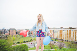 Young beautiful blonde caucasian girl playing with colorful  heart shape balloons with city in background, looking in camera smiling - childhood, carefreeness concept