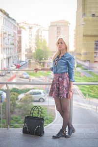Young beautiful blonde caucasian girl posing outdoor in the city leaning on a windowsill wearing a jeans shirt, a bag and a floral skirt overlooking on her right - youth, freshness concept