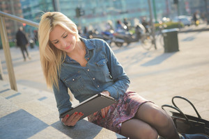 Young beautiful blonde caucasian girl seated on a staircase using a tablet and smartphone looking downward the screen - communication, technology, social network concept