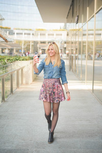 Young beautiful blonde caucasian girl using a smartphone taking a selfie while walking through the street of the city - communication, technology, social network concept