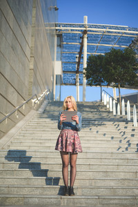 Young beautiful blonde caucasian girl using a tablet connected online on a staircase outside in the city wearing jeans shirt and floral skirt - technology, communication, social network concept