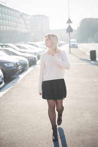 Young beautiful blonde caucasian girl walk through the city at dusk. She is wearing a white sweater and a black skirt.