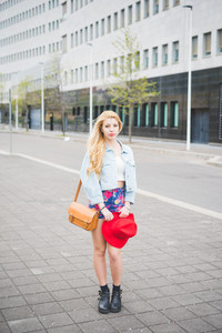 Young beautiful blonde caucasian girl walking in the city suburbs dressed with a red hat, a pair of floral shorts and a jeans jacket