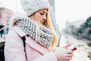 Young beautiful blonde caucasian woman holding a smart phone, looking down and tapping the screen - technology, social network, communication concept