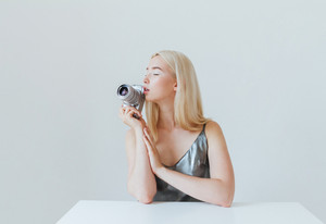 Young beautiful blonde girl in silver dress holding camera and sitting at white table isolated on the grey background